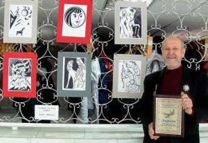 Жорж Иванович Шанаев рядом со своими картинами.