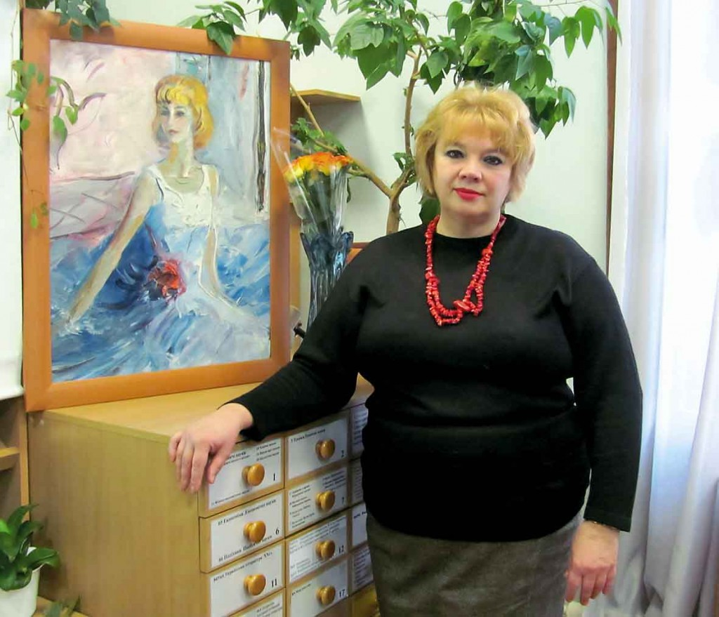 Поет Наталія Савіна поряд з портретом мами, Маргарити Єніцької.