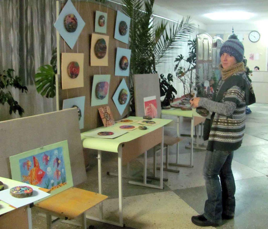 Тетяна Чернікова, мама Тараса Охременко, готовить картини на пнях до розвішування.